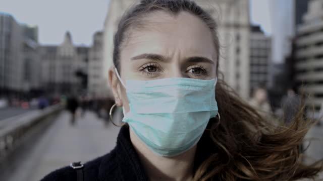 stockvideo's en b-roll-footage met panning rond jonge vrouw die gezichtsmasker draagt terwijl uit in de straten van londen - ongerustheid