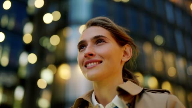 vidéos et rushes de panoramique plan rapproché de jeune femme confiante dans le trench-coat restant dans la rue de ville entourée par des lumières de bokeh et regardant loin rêveusement avec le sourire heureux sur le visage, ses cheveux agitant dans le vent - attendre