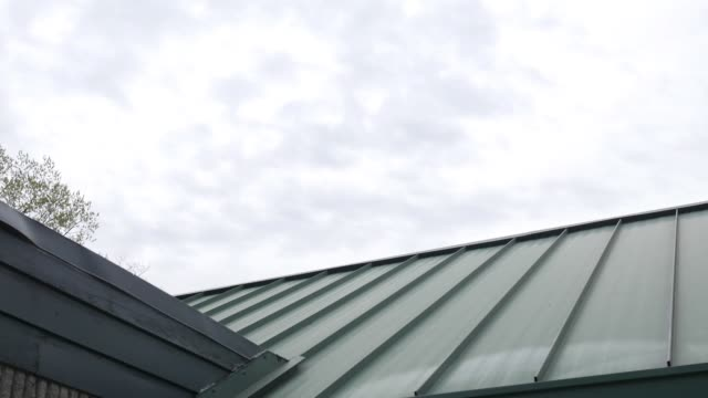 Panning down over a green metal roof on a building Panning down over a green metal roof on a building metallic stock videos & royalty-free footage