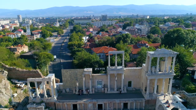 panning drone shot of the ancient roman amphitheater in the old town of plovdiv, bulgaria - bułgaria filmów i materiałów b-roll
