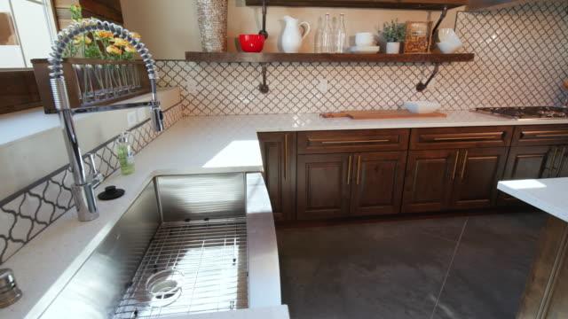 panning from kitchen sink to reveal modern kitchen - мозаика стоковые видео и кадры b-roll