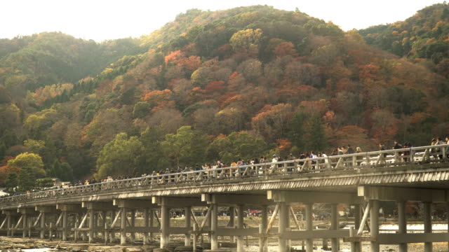 vídeos de stock e filmes b-roll de panning from low angle view: togetsukyo bridge in kyoto, japan amid autumn in weekend - prefeitura de quioto