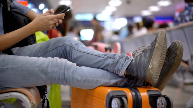 Panning from Shoe to Face of Asian man who using smartphone when he waiting flight in airport