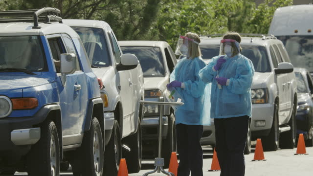 Panning Long Shot of Two Female Nurses Wearing Gowns, Surgical Face Masks, Gloves, and Face Shield Talking to Patients in their Cars in a Drive-Up (Drive Through) COVID-19 (Coronavirus) Testing Line Outside a Medical Clinic/Hospital Outdoors (Second Wave)