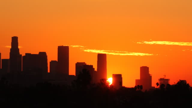 Panning Los Angeles Sunrise Time Lapse Beautiful panning time lapse of the sun rising from behind downtown Los Angeles. Birds and planes carefully removed. sunrise dawn stock videos & royalty-free footage
