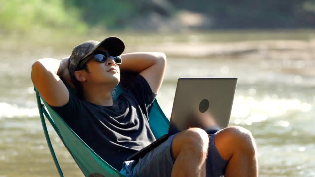Panning Man relaxing on picnic chair in the river with laptop. video