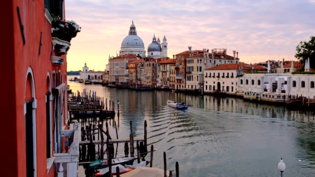 Panning motion of passing motorboat. Beautiful sunrise view of Grand Canal and Basilica di Santa Maria della Salute.