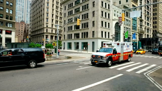 Panning: New York City Fire Department Ambulance rides with siren on.