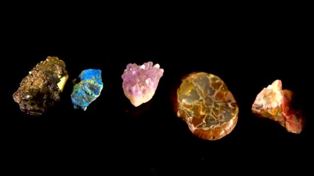 panorering av färgglada sällsynta mineraler och stenar på en svart bakgrund - mineral bildbanksvideor och videomaterial från bakom kulisserna