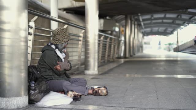 Panning of Homeless senior men sitting on the footpath.
