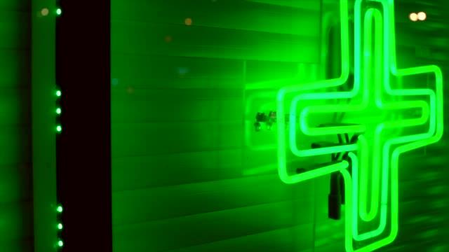 följning av marijuana apotek neongrön ogräs cross på stadens store främre fönster - hasch bildbanksvideor och videomaterial från bakom kulisserna