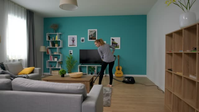 Panning of young beautiful woman vacuuming her cozy apartment video