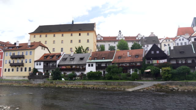 panning: old-styled house along river in Cesky Krumlov town under white sky