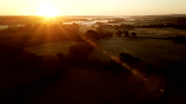 Panning over English countryside at dawn Slowly panning up and over the English countryside at dawn sunrise dawn stock videos & royalty-free footage