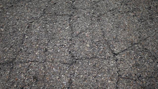 vídeos de stock e filmes b-roll de panning over old crumbling concrete parking lot texture - driveway, no people
