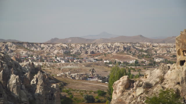 panning panoramic view of the small modern village and valley in Goreme village, Turkey on a clear sky and sunny day. Rural Cappadocia landscape. Volcanic mountains in Goreme national park. Countryside lifestyle.