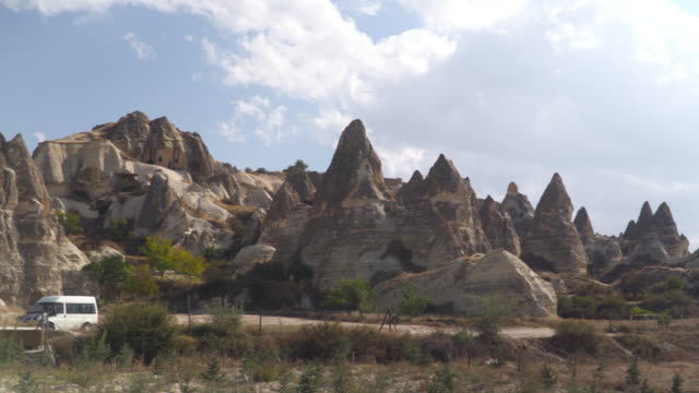 panning panoramic view of the valley as an eroded resident building in Goreme village, Turkey on a clear sky and sunny day. Rural Cappadocia landscape. Volcanic mountains in Goreme national park. Countryside lifestyle.