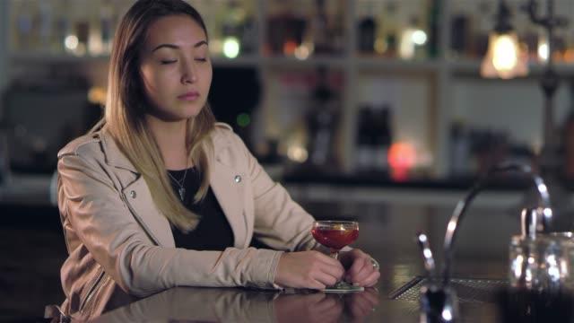 vídeos de stock, filmes e b-roll de garimpando o retrato de uma jovem mulher asiática atraente tomar um gole de sua bebida e olhando para a câmera em um bar - costumer