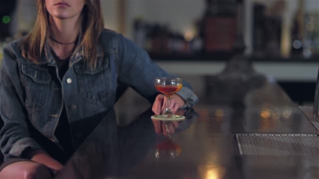 vídeos de stock, filmes e b-roll de garimpando o tiro do retrato de uma jovem mulher loira atraente olhar para a câmera em um bar - costumer