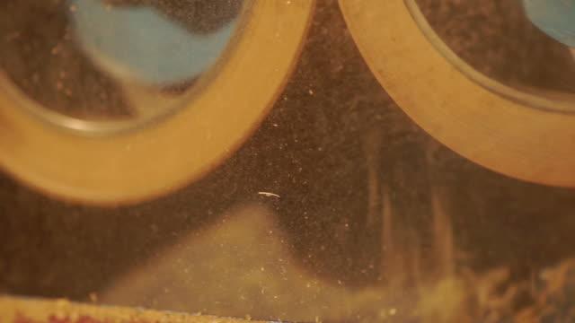 panorering höger kamera av fräs processen för att producera brunt ris av gummi-rullen huller att ta bort skalet från paddy. - skalhylsa bildbanksvideor och videomaterial från bakom kulisserna