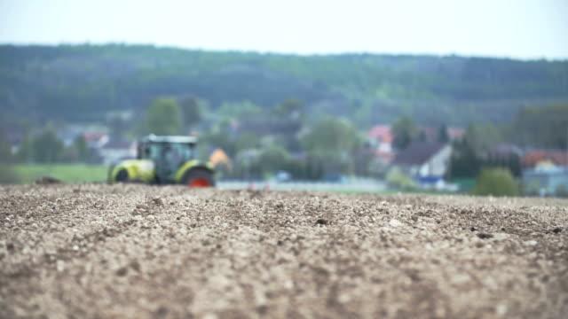 vidéos et rushes de panoramique de pousse du champ labour tracteur avec herses. - seigle grain