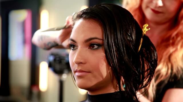 Panorámica toma como el estilista cortes de una mujer joven de pelo - vídeo