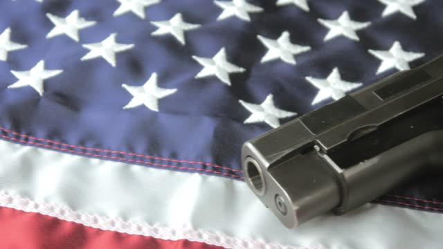 панорамирование выстрел из ручное оружие лежа на американский флаг - debate стоковые видео и кадры b-roll