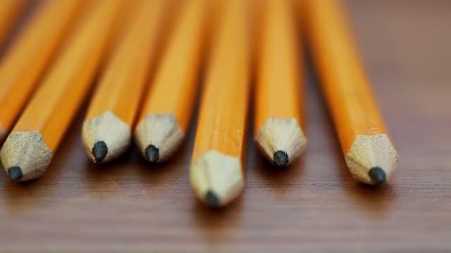 en panorering skott av en rad pennor som vilar på ett träbord - blyertspenna bildbanksvideor och videomaterial från bakom kulisserna
