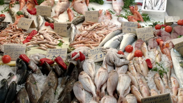 panning shot of a variety of seafood at athens central market - banchi di pesci video stock e b–roll