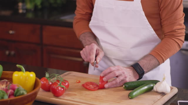 Panning shot of an old chef slicing a tomato on a cutting board video