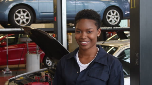 Panning shot of cheerful young woman in college learning to be a mechanic video