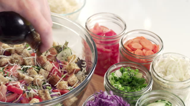 신선한 정원 샐러드에 요리사 이슬비 샐러드 드레싱의 이동 - 식초 스톡 비디오 및 b-롤 화면