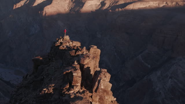 4K Panning shot of Male tourist standing on rock pinnacle taking in the view of Fish River Canyon video