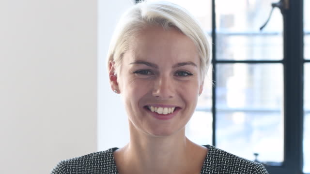 vídeos de stock e filmes b-roll de panning shot of mid adult businesswoman smiling towards camera - cabelo louro