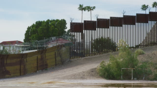 Panning Shot of Parts of the Old and New Steel-Slat Border Wall Topped by Razor Wire (on the US Side) between Mexico and the United States with the Town of Los Algodones and Palm Trees on the Other Side and Bushes in the Foreground