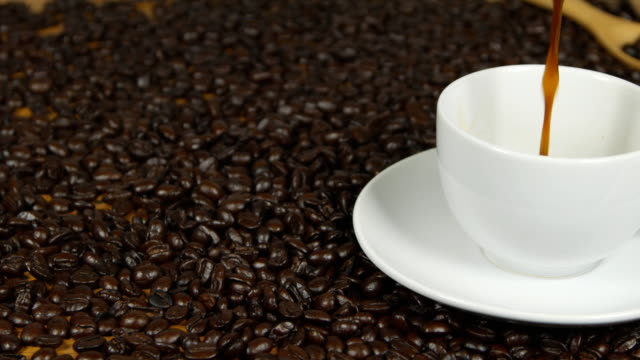 panning shot of Pouring coffee from coffee pot in white cup surrounded by coffee beans video