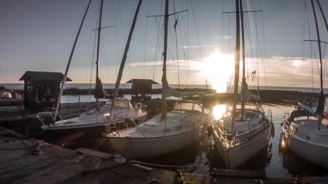 vídeos y material grabado en eventos de stock de tiro panorámico de veleros en un puerto en dinamarca al atardecer - amarrado