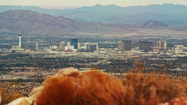 panning shot of the las vegas skyline with mountain ranges in the background (frenchman mountain, sunrise mountain, muddy mountains) - las vegas video stock e b–roll