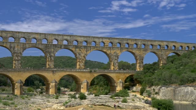panning shot of the pont du gard, ancient roman aqueduct in the southern france, with beautiful blue cloudy skies in the background. 4k, uhd - stile classico romano video stock e b–roll