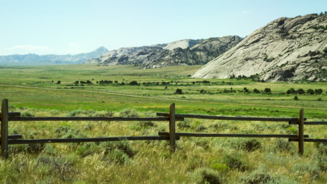 Panning Shot of the Wind Blowing Wild Grasses of a Wyoming Valley with a Wooden Fence in the Foreground and Rocky Mountains in the Distance under a Clear, Sunny Sky