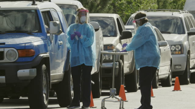 vidéos et rushes de panoramique shot of two female nurses wearing gowns, surgical face masks, gloves, and face shield talking to patients in their cars in a drive-up (drive through) covid-19 (coronavirus) testing line outside a medical clinic/hospital outdoors (second wave) - test médical