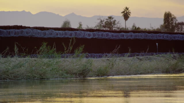 Panning Shot of Water Flowing Down a Canal Running Parallel to the Steel-Slat Border Wall (on the US Side) between Mexico and the United States Topped by Razor Wire on a Partly Cloudy Day at Sunset