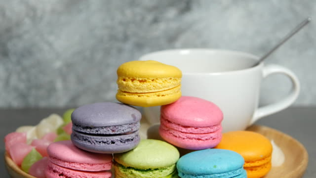 panning shot of white cup of hot coffee and colorful macaroons dessert food on dish video