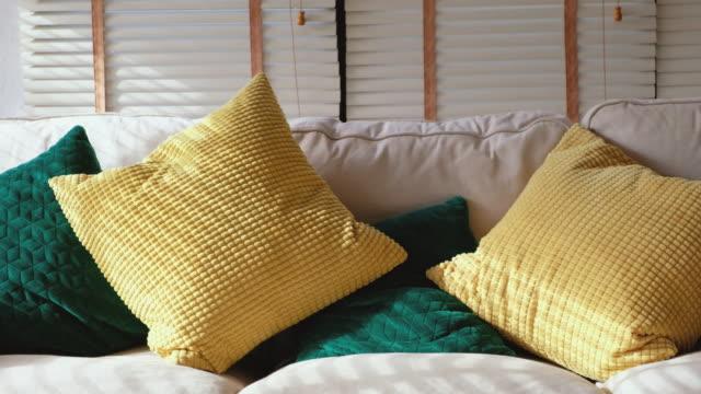 vídeos y material grabado en eventos de stock de panning shot de almohada amarillo y verde sobre blanco sofá en salón - almohada
