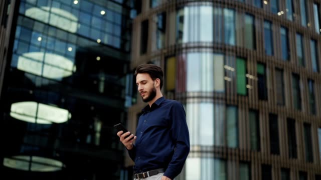 panning slow motion shot of confident young businessman text messaging on cell phone while standing in city street with hand in pocket and looking away thoughtfully, low angle view - distrarre lo sguardo video stock e b–roll