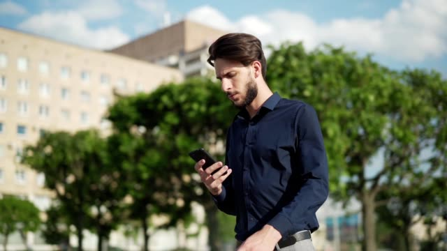 Panning slow motion shot of determined young businessman text messaging on cell phone and walking down street confidently