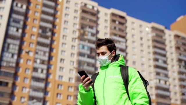 panning zeitlupe schuss von jungen männlichen lebensmittelkurier in medizinischer maske mit navigations-app auf handy, während zu fuß die straße mit isolierten tasche liefert ordnung - smartphone mit corona app stock-videos und b-roll-filmmaterial