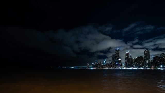 Panning timelapse of the skyline as clouds roll by over the city of Chicago on a cold winter evening with Lake Michigan in the foreground and building lights and street lamps lighting up the night. video