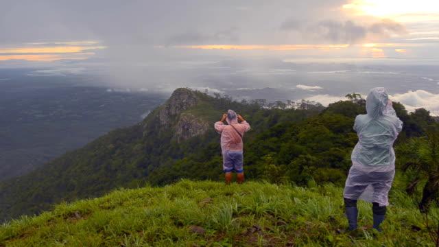 panning: traveler in rain season on the mountain peak video