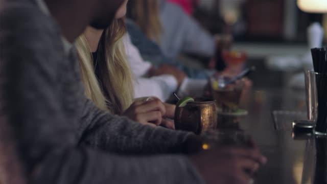 vídeos de stock, filmes e b-roll de garimpar para cima tiro de um homem sentado entre as pessoas e olhando para o telefone em um bar - costumer